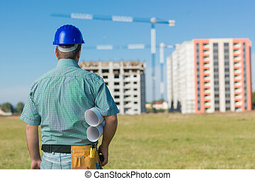 engineer looking at building in construction