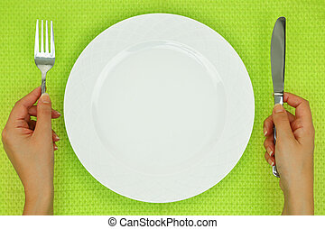 Hands with fork and knife and empty plate on the table
