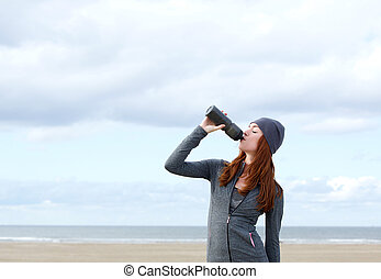 Healthy young woman drinking water from bottle