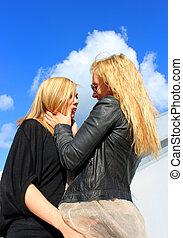 women flirting - two beautiful women flirting in the...