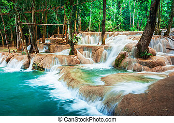 Jangle landscape with turquoise water of Kuang Si waterfall...