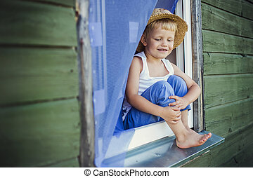 Young boy sit on the window sill