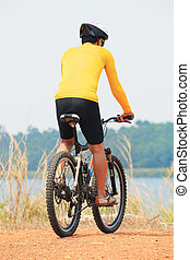 rear view of young bicycle man wearing rider suit and safety...
