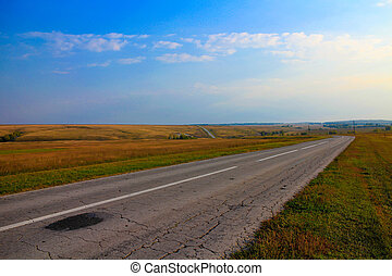 asphalt road disappearing into the horizon on background of...