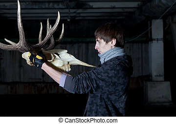 Young man with a sharp deer skull in a dark basement