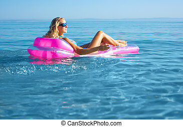 Blonde woman with inflatable raft