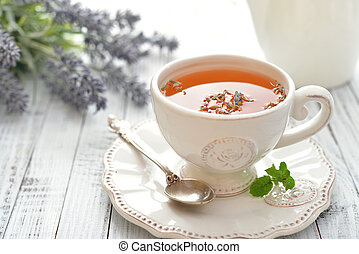Lavender tea in cup closeup on wooden background
