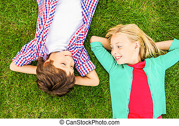 Enjoying summer time. Top view of two cute little children holding hands behind head and looking at each other with smile while lying on the green grass together