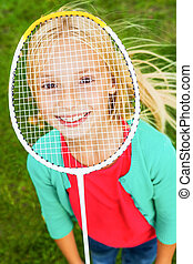 I am ready to play! Top view of cute little girl hiding her face behind badminton racket and smiling while standing on green grass