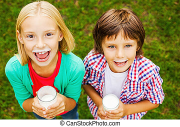 We love milk. Top view of two cute little children with milk...