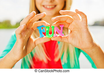 Just for fun! Close-up of cheerful little girl holding colorful plastic letters in her hands and smiling while standing outdoors sun