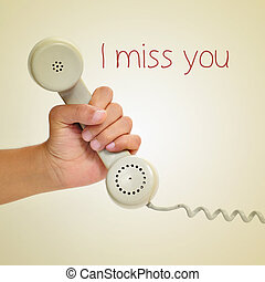 I miss you - a man hand holding the handset of a telephone...