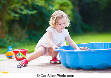 Little girl playing with sand - Cute curly toddler girl in a...