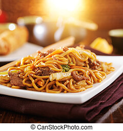 chinese beef lo mein with orange glow in background
