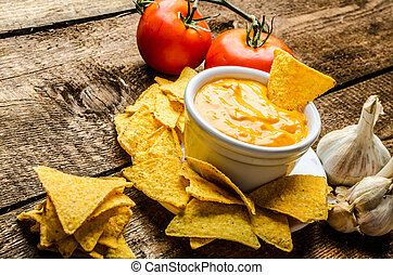 Tortilla chips with tomato and cheese-garlic dip on wood old...