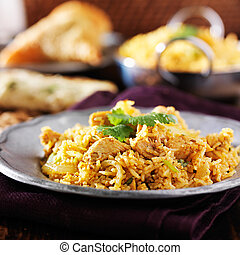 indian chicken biryani with naan and samosa in background
