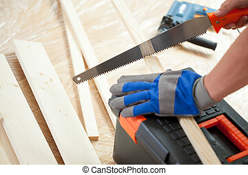 Using hand saw during house renovation - Close-up of using...