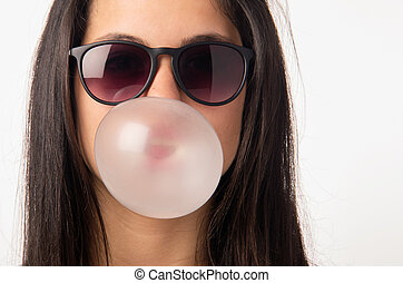 Gum Girl - Brunette teenager girl with sunglasses blowing a...