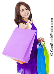 asian smiling young woman holding shopping bags over white...