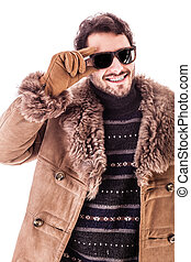 Sunglasses and coat - a cheerful young man wearing an...