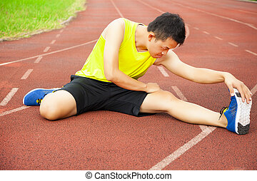 young man sitting on the track and stretching his leg to...