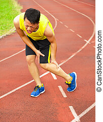 young male runner suffering from leg cramp on the track in...