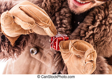 Unwrapping - a young man wearing a sheepskin coat and...