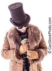 Pocketing dollars - a young man wearing a sheepskin coat and...