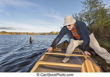 launching canoe on a lake
