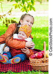 Little girl and little boy in autumn park with apples