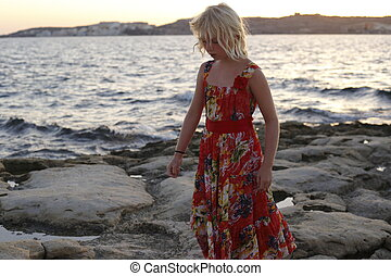 girl is walking along the coast on evening
