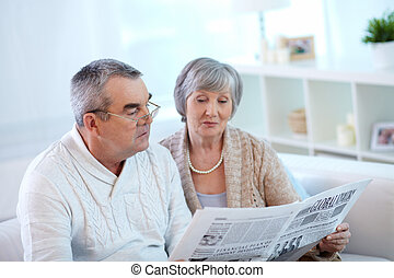 Seniors reading paper - Senior couple reading newspaper...