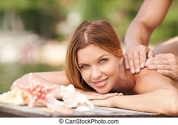 Massage on the beach - Young woman receiving massage from...