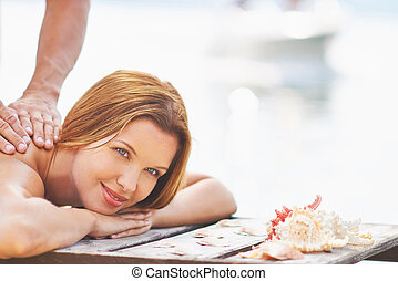 Outdoor massage - Young woman receiving massage on summer...
