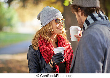 Hot coffee together - Young couple drinking coffee outdoors...