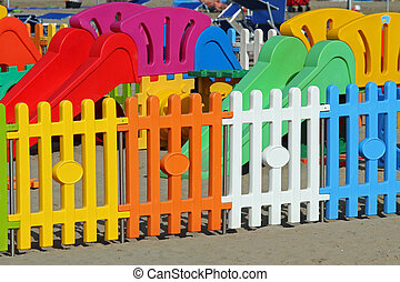 fence a playground on the beach tourist village - colorful...