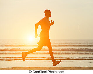 One man running on beach with sunset in background