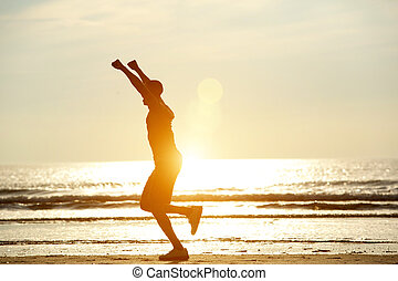 One man running on beach with arms raised in celebration