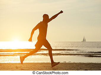 One man running on beach with hand raised and sunset in...
