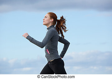 Healthy young woman running outdoors - Portrait of a healthy...