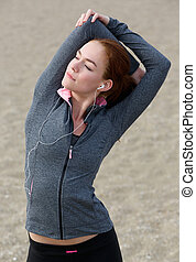 Young woman stretching muscles outdoors - Close up portrait...
