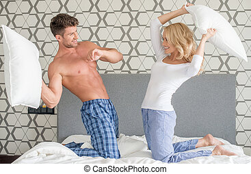 Playful couple having a pillow fight - Playful attractive...