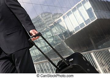 hand of businessman holding the trolley, business trip -...