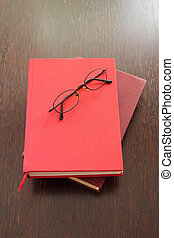 Eyeglasses and two red books laying on wood table