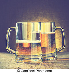 Beer mugs on the wooden table. Retro style filtred