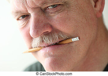 Older man with pencil in his teeth