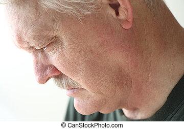 Depressed older man looking down - Downcast senior man with...
