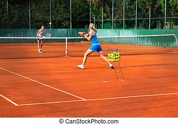 Two young women playing tennis outdoors on Two young womwn...