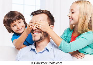 Guess who? Two playful kids covering eyes of their cheerful...