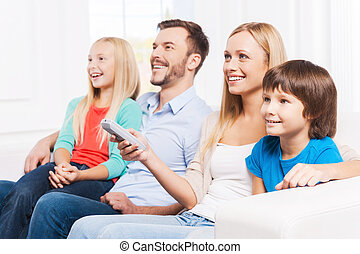 Watching their favorite show Side View of happy family of...